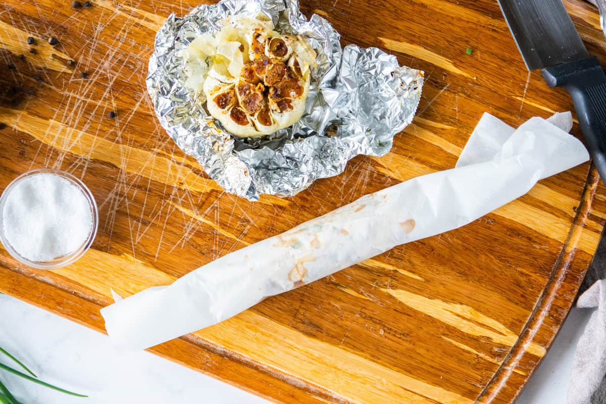 compound butter is wrapped in white wax paper on a cutting board with a head of roasted garlic.