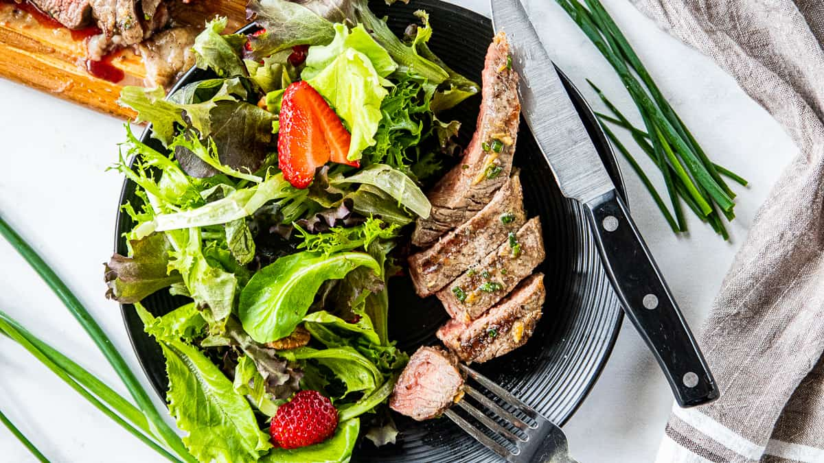 Top down view of sliced steak next to a salad on a black plate.