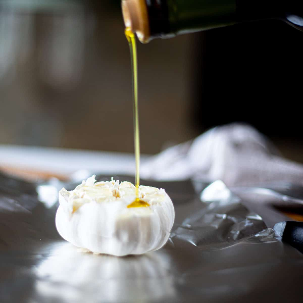 A head of garlic on tin foil with olive oil being drizzled onto it.