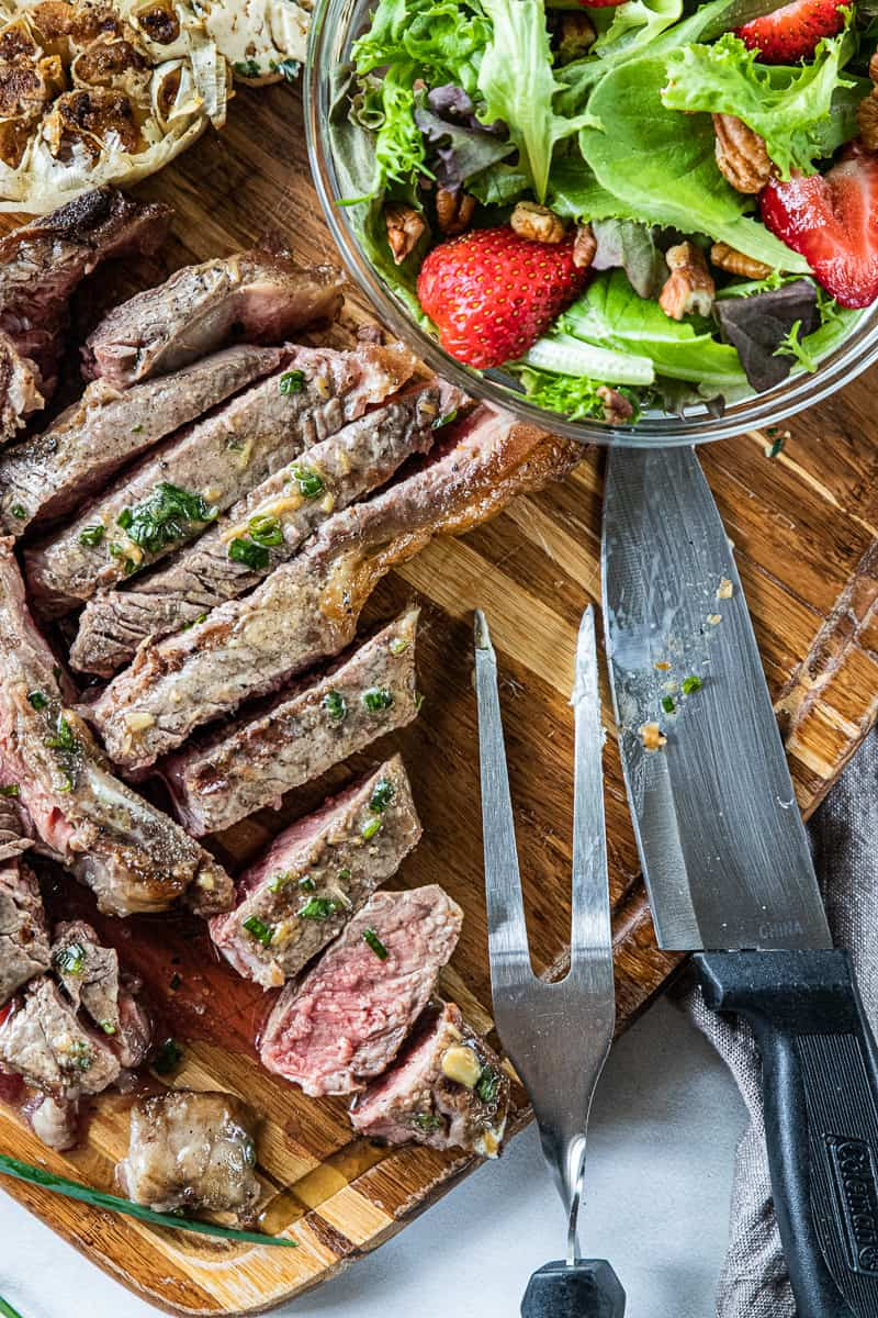 a porterhouse steak shown sliced on a cutting board next to a salad with strawberries.