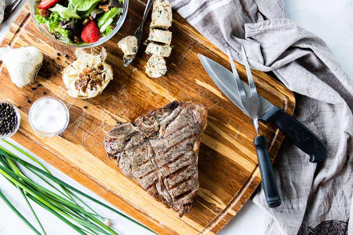 Top down view of a grilled porterhouse steak on a cutting board next to some salt and pepper, roasted garlic and a steak knife.