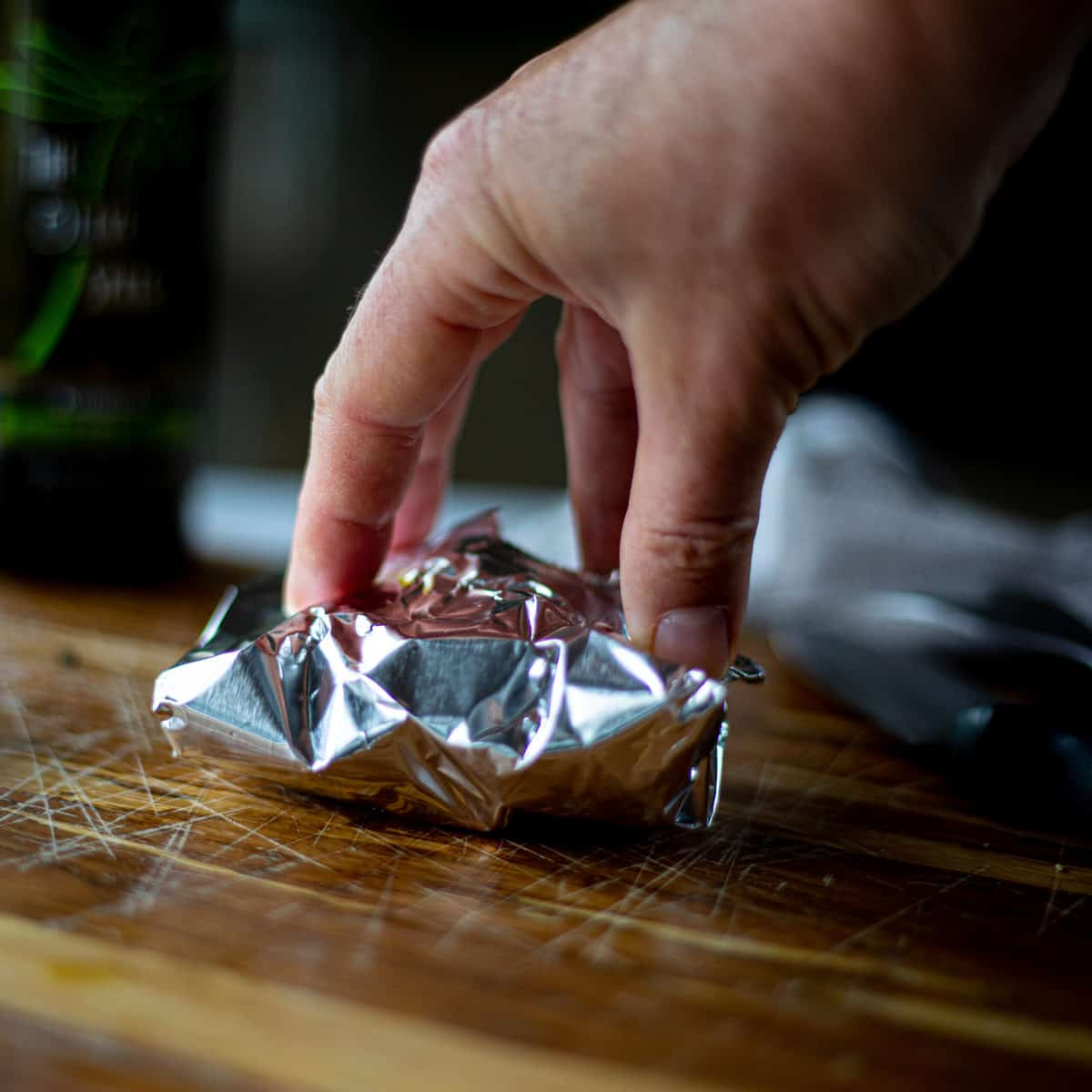 A hand sealing a tin foil packed shut on a cutting board.