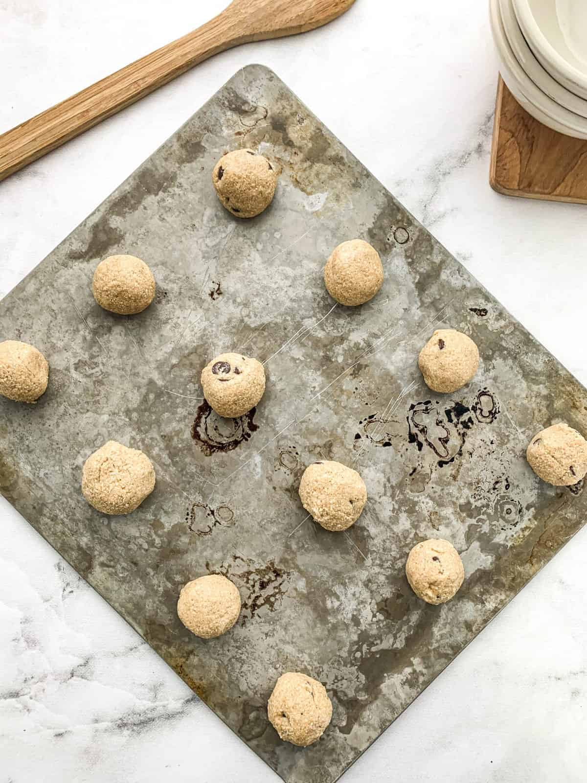 raw cookie dough bites rolled into balls on a flat cookie tray.