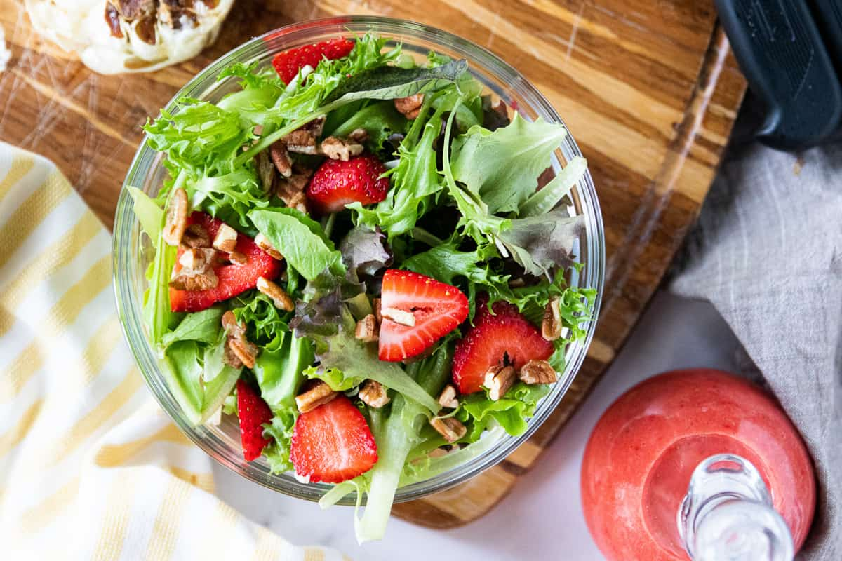 A top down view of a lettuce salad with sliced strawberries and pecans with strawberry vinaigrette in a glass jar next to it.