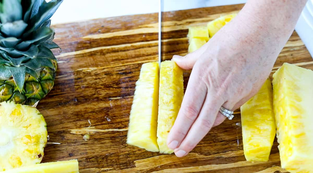 A fresh pineapple section is being cut in half.