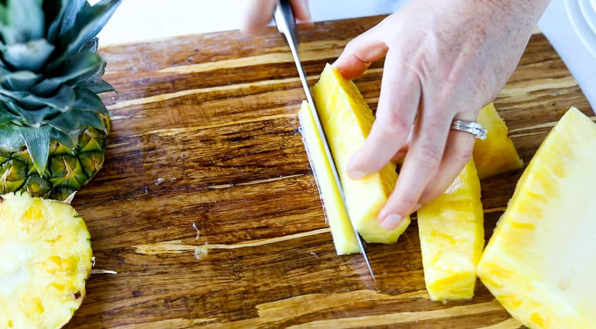 Several pineapple sticks are on a cutting board with the core being cut away from them.