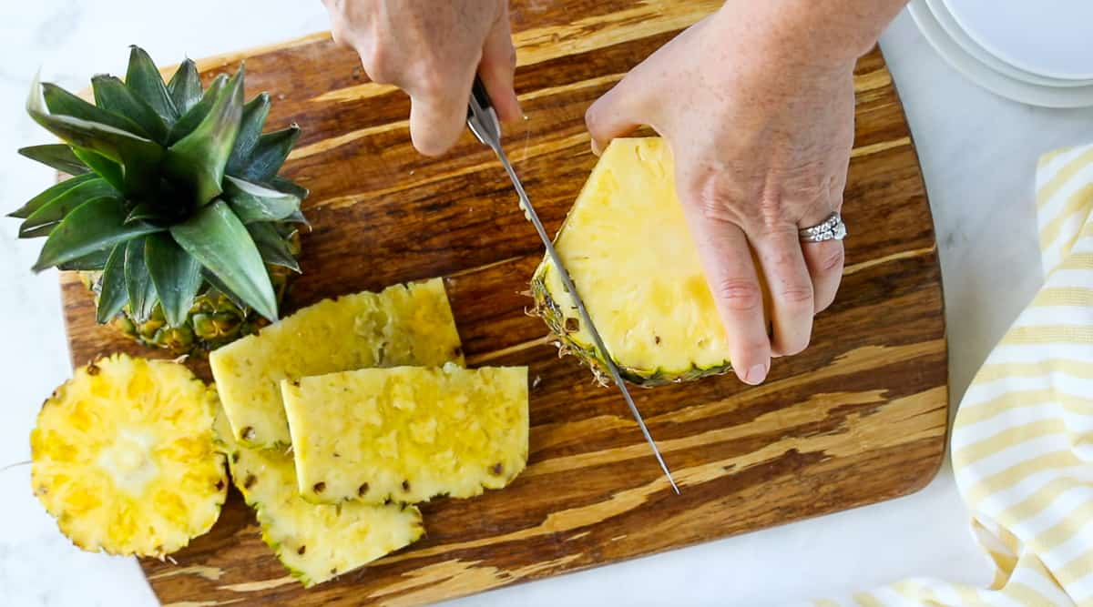 A top down view of a pineapple standing upright on a cutting board with the top and bottom cut off and the outside layer being cut off with a chefs knife.