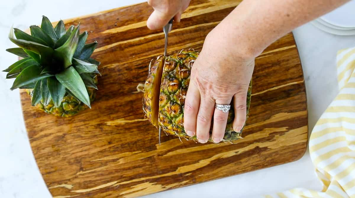 A top down view of a pineapple bottom being cut off with a chefs knife.