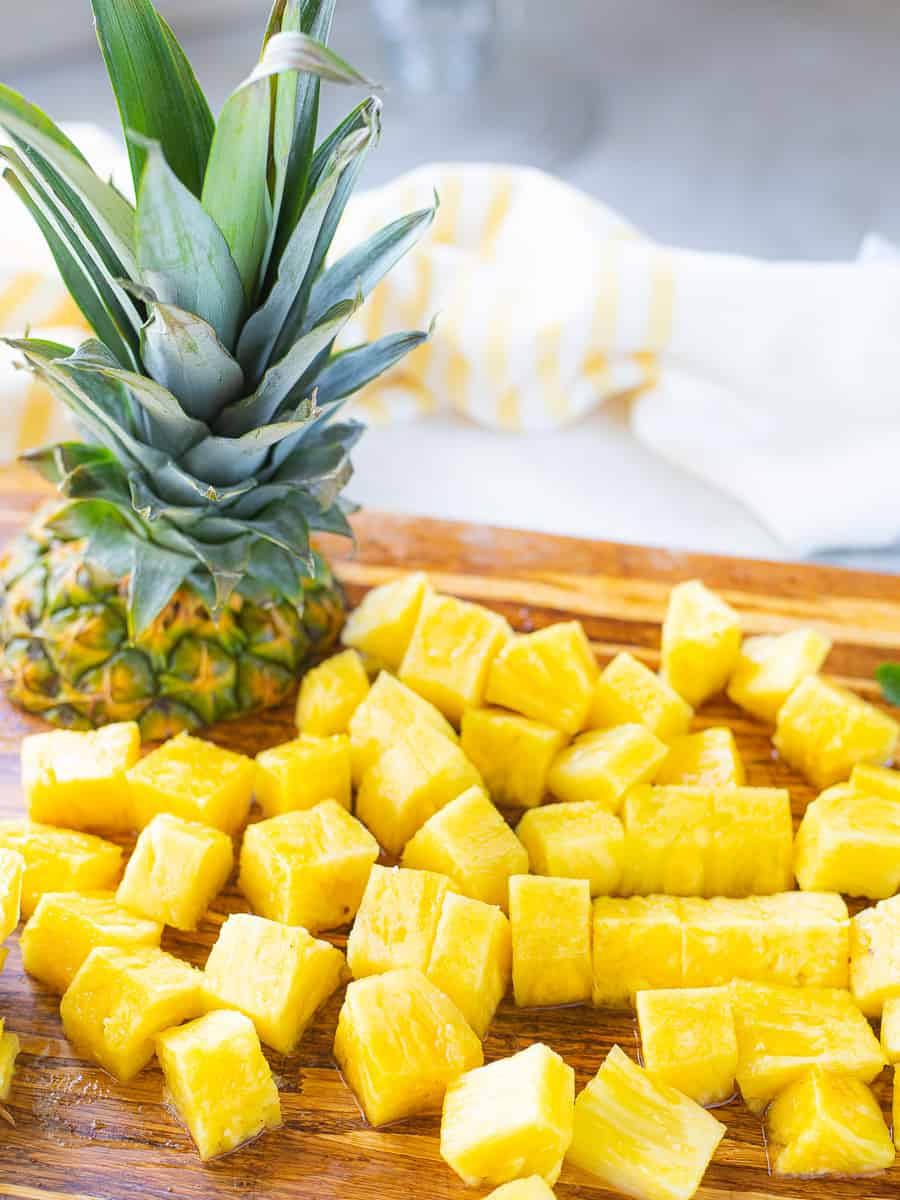 Cubed fresh pineapple on a cutting board next to a top of a pineapple.