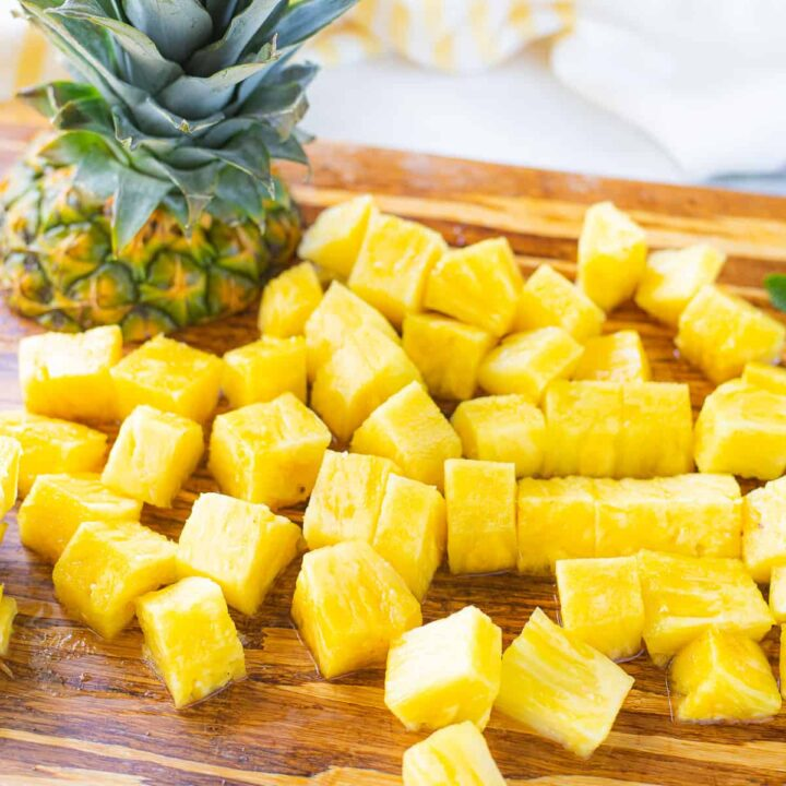 Fresh pineapple cubes on a cutting board next to the top of a pineapple.