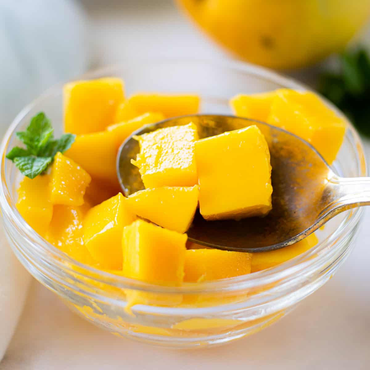 A clear bowl of diced mango chunks with a spoon holding 3 cubes with a mint garnish.