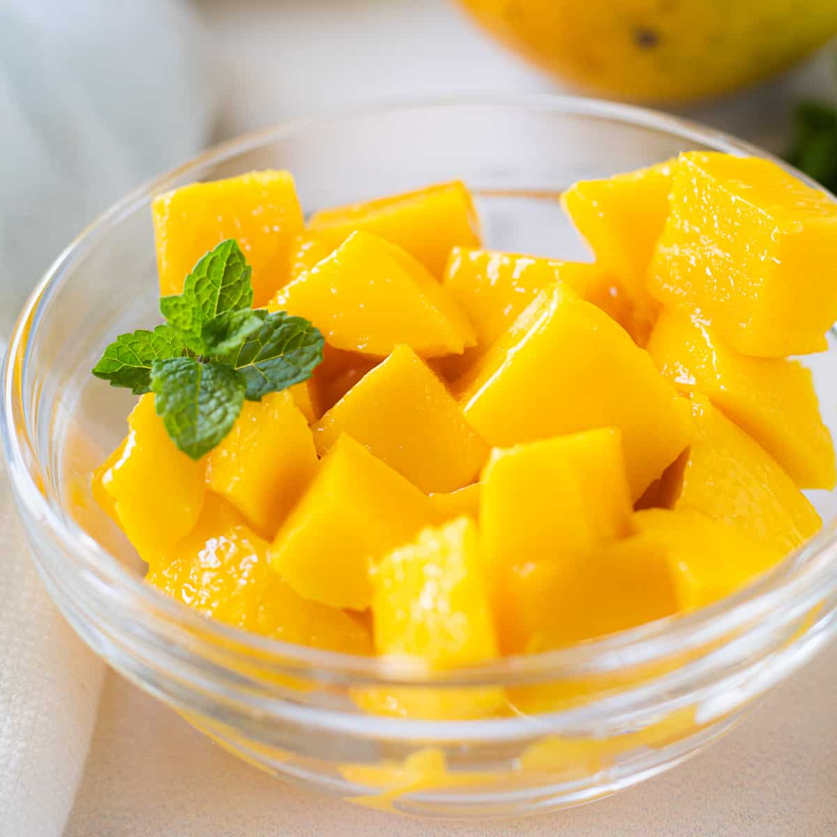 A close up of a bowl of cubed mango in a clear glass dish.