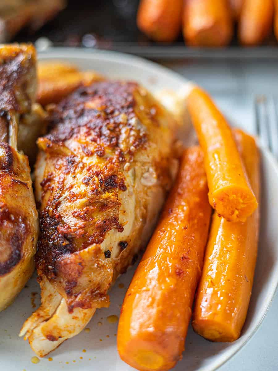 A cooked whole chicken on a serving dish with cooked carrots.