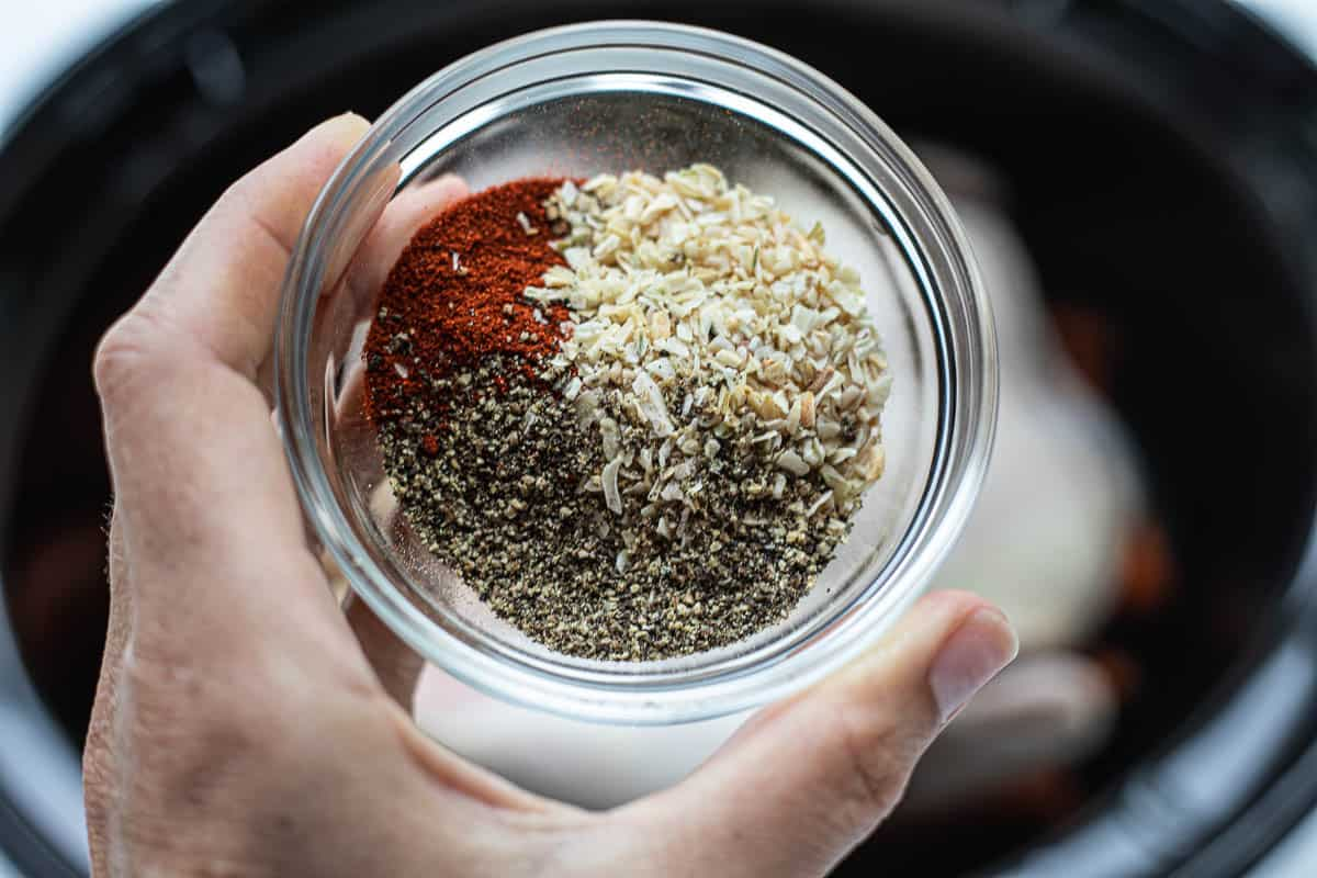 A small jar filled with a combination of spices.
