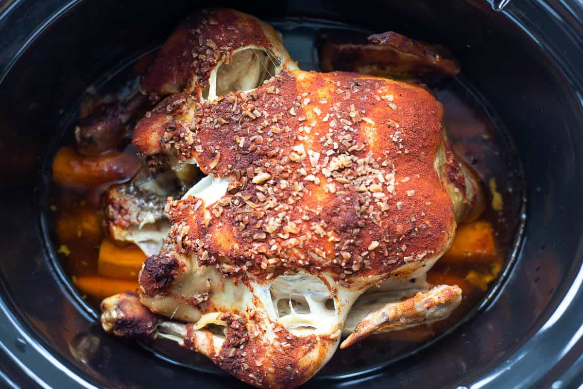 A cooked whole chicken and cooked carrots in the base of a slow cooker.