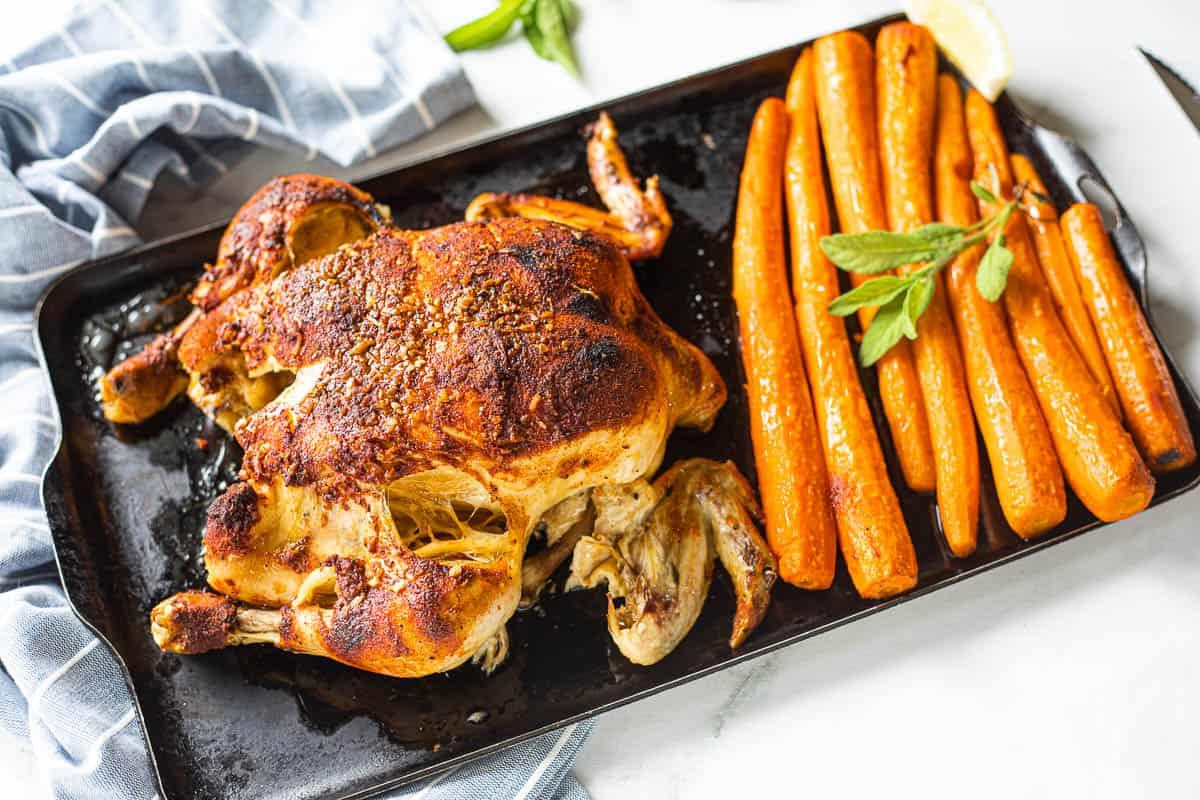 A cooked whole chicken on a baking sheet with cooked carrots.