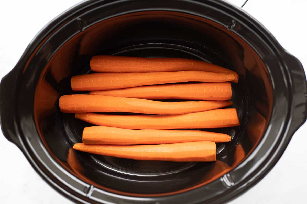 Peeled, fresh carrots placed in the base of a black slow cooker.