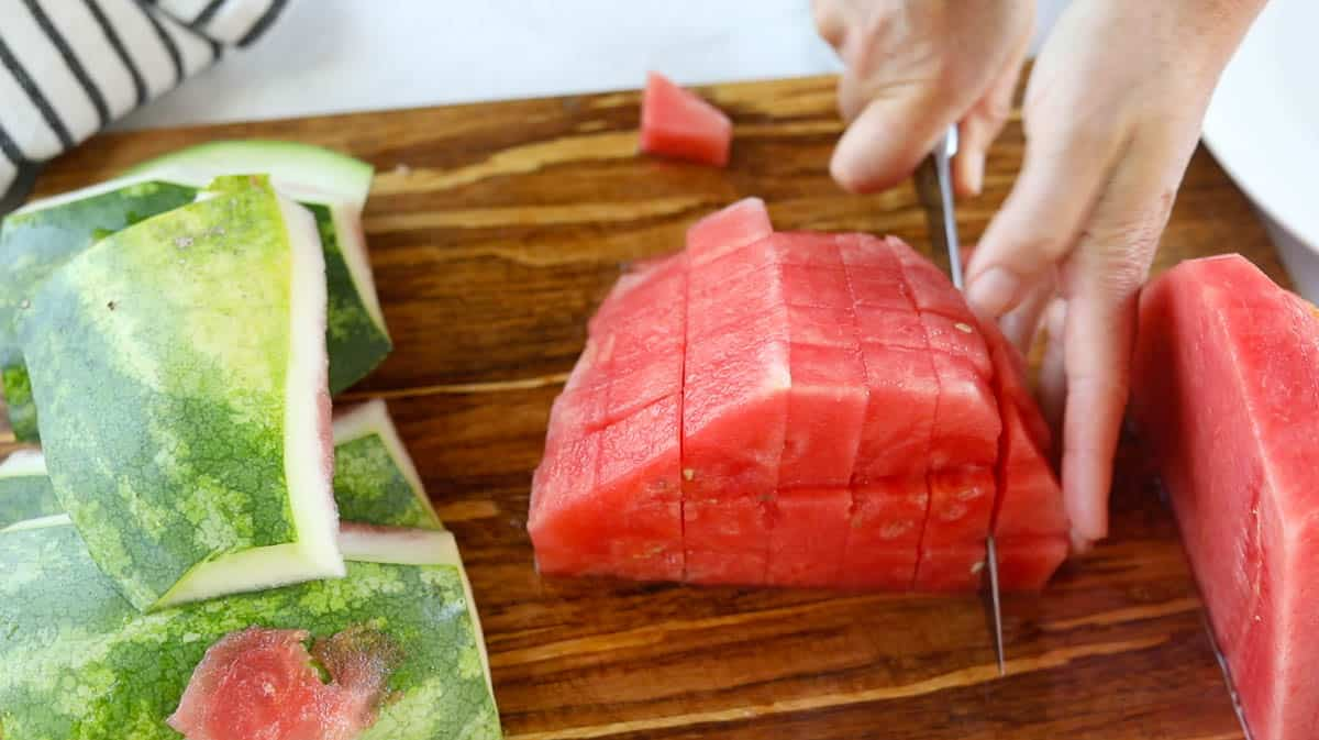 Half a watermelon being cut into cubes with a knife.