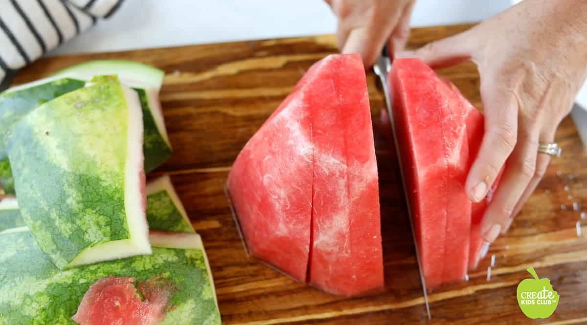 Half of a sliced watermelon with no rind getting divided.