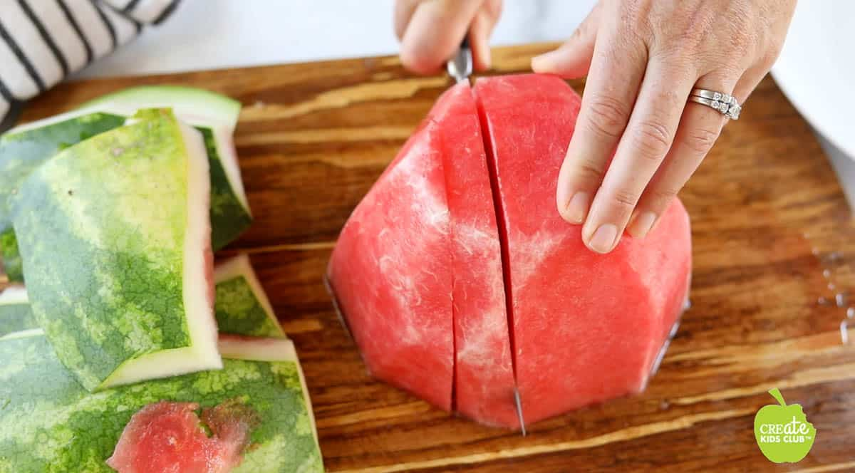 Half of a watermelon with no rind on a cutting board getting cut into large slices.
