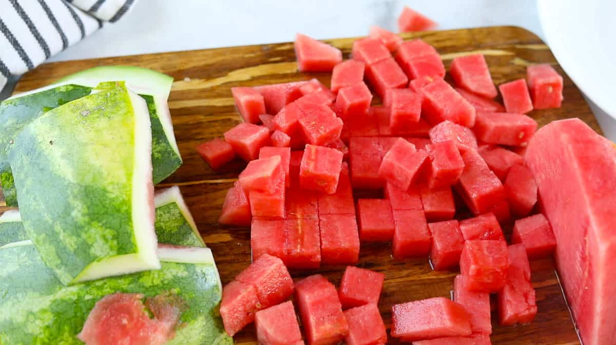Sliced watermelon cubes on a cutting board next to the rind.