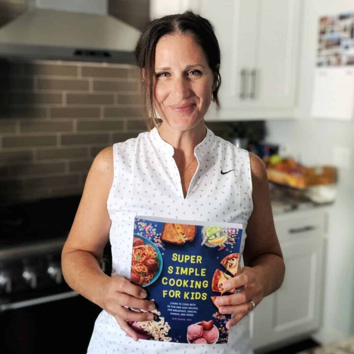 A woman standing in a kitchen holding a cookbook