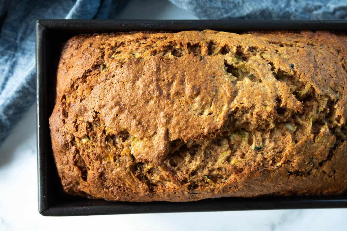 A loaf of banana zucchini bread  in a loaf pan on top a dish towel all on top of a granite countertop.