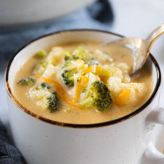 A bowl of soup with broccoli and cauliflower