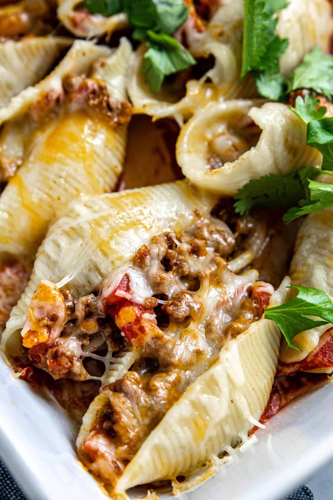 Mexican stuffed shells baked in a white casserole dish.