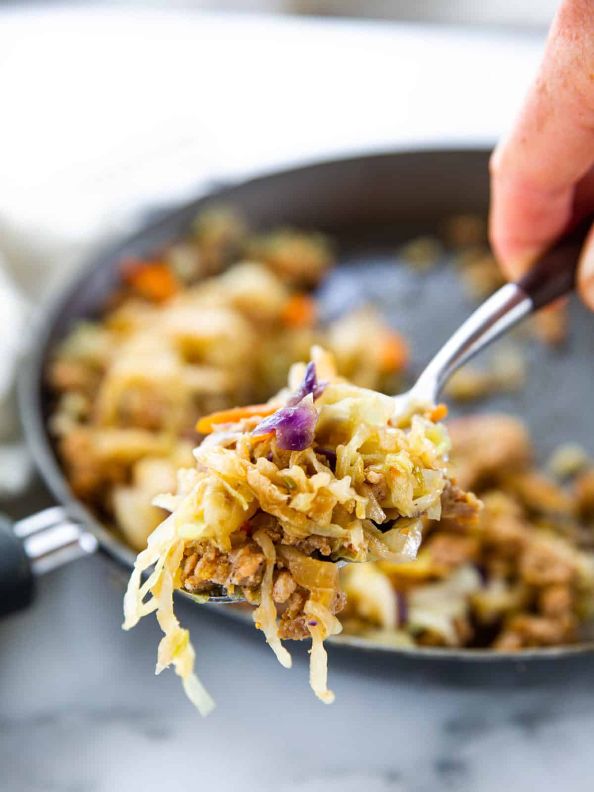 Pork egg roll stuffing shown up close on a serving spoon with the rest of the pan blurred in the background.
