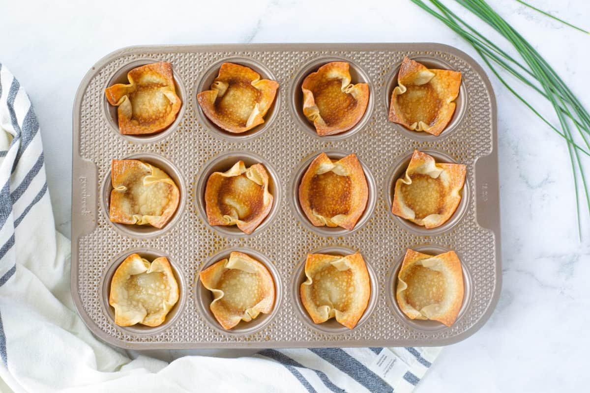 "Baked wonton wrappers in a 12 cup muffin tin after being baked into ""cups""."