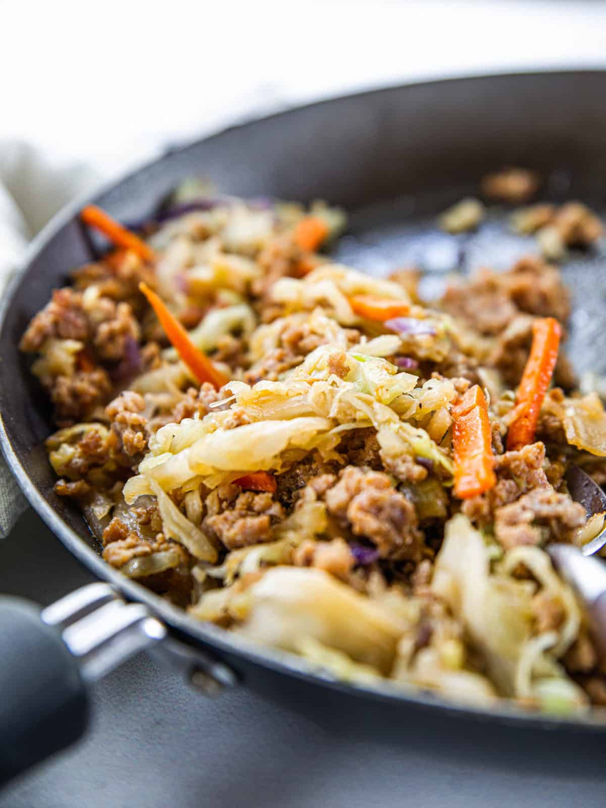 Pork egg roll stuffing shown cooked in a skillet up close.