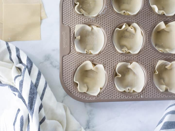 Uncooked wonton wrappers formed into muffin tin to shape them into cups after baking.