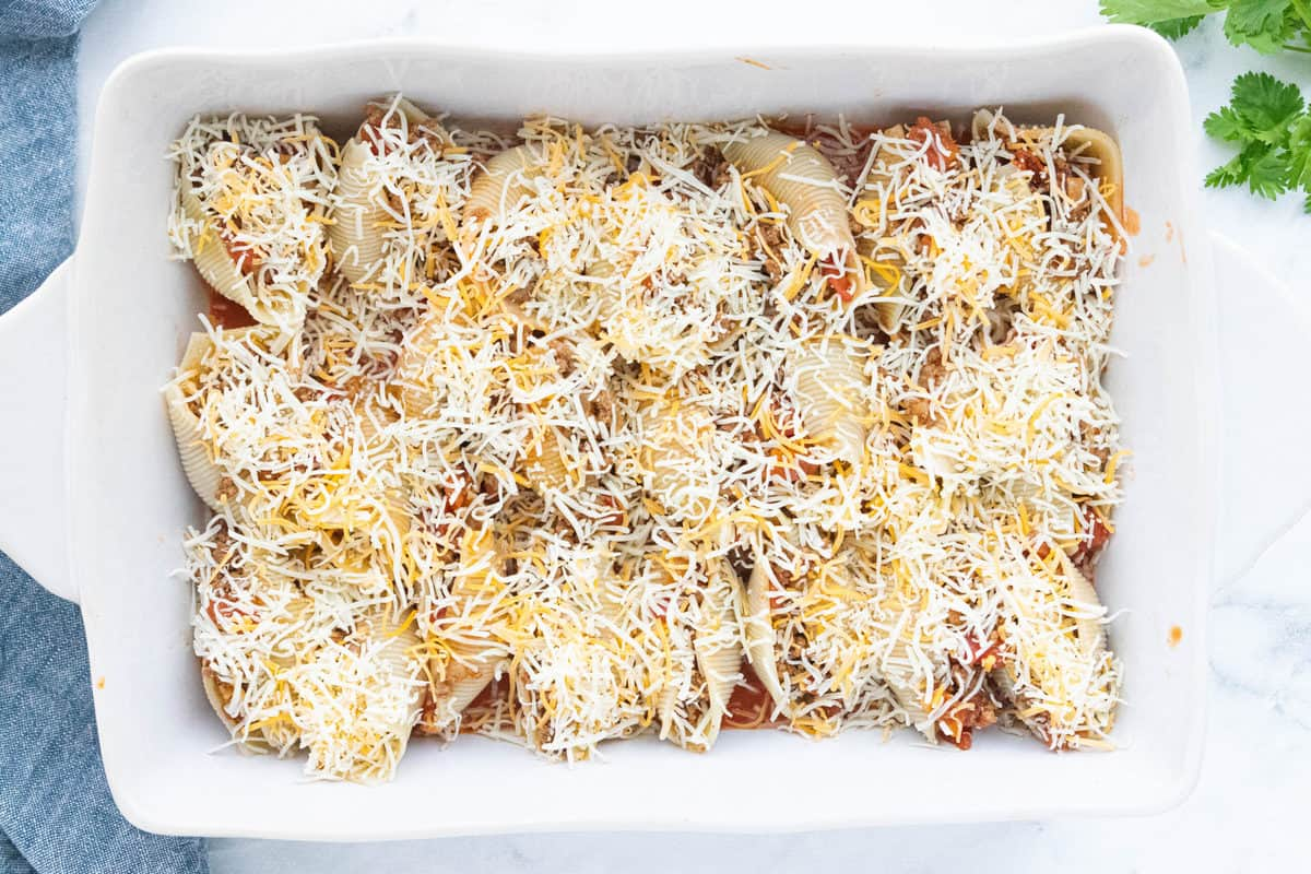 Stuffed shells placed on top of enchilada sauce with shredded cheese sprinkled over the top of the shells in a white baking dish.