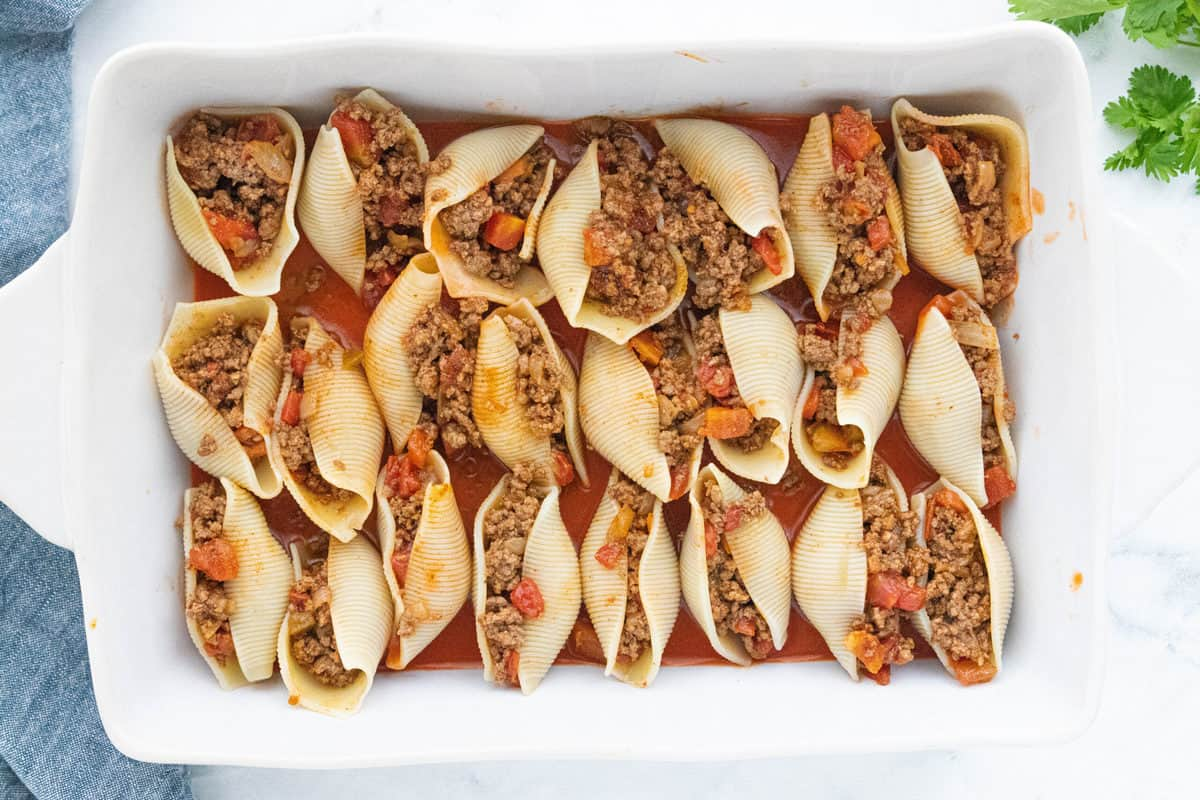Stuffed shells placed on top of enchilada sauce in a white baking dish.