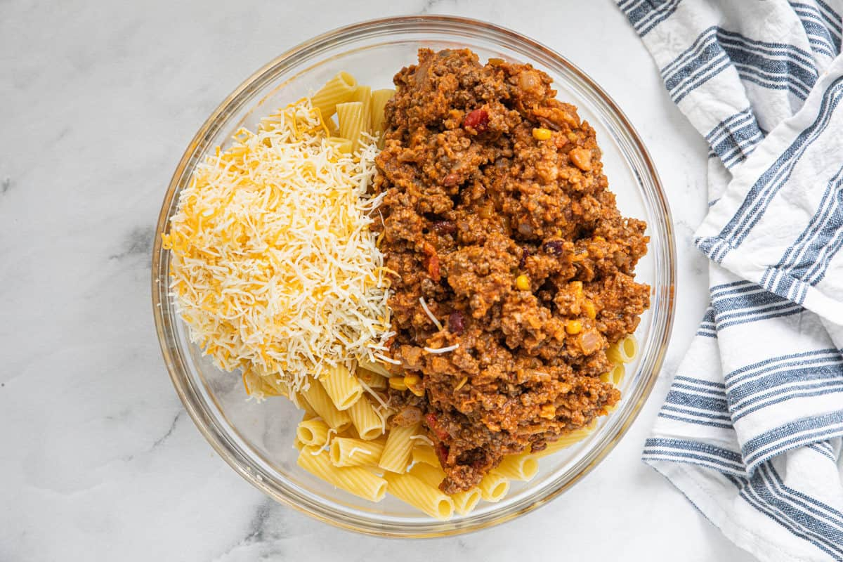 Taco pasta ground meat, Mexican-style shredded cheese and rigatoni pasta in a large glass bowl on a granite countertop with a dish towel next to the bowl.