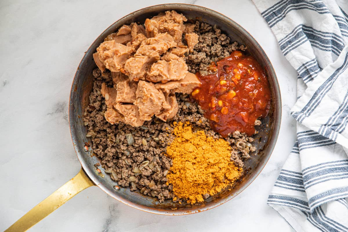 Ground beef, refried beans, salsa and taco seasoning being shown in a large skillet on a granite countertop with a dish towel next to the skillet.