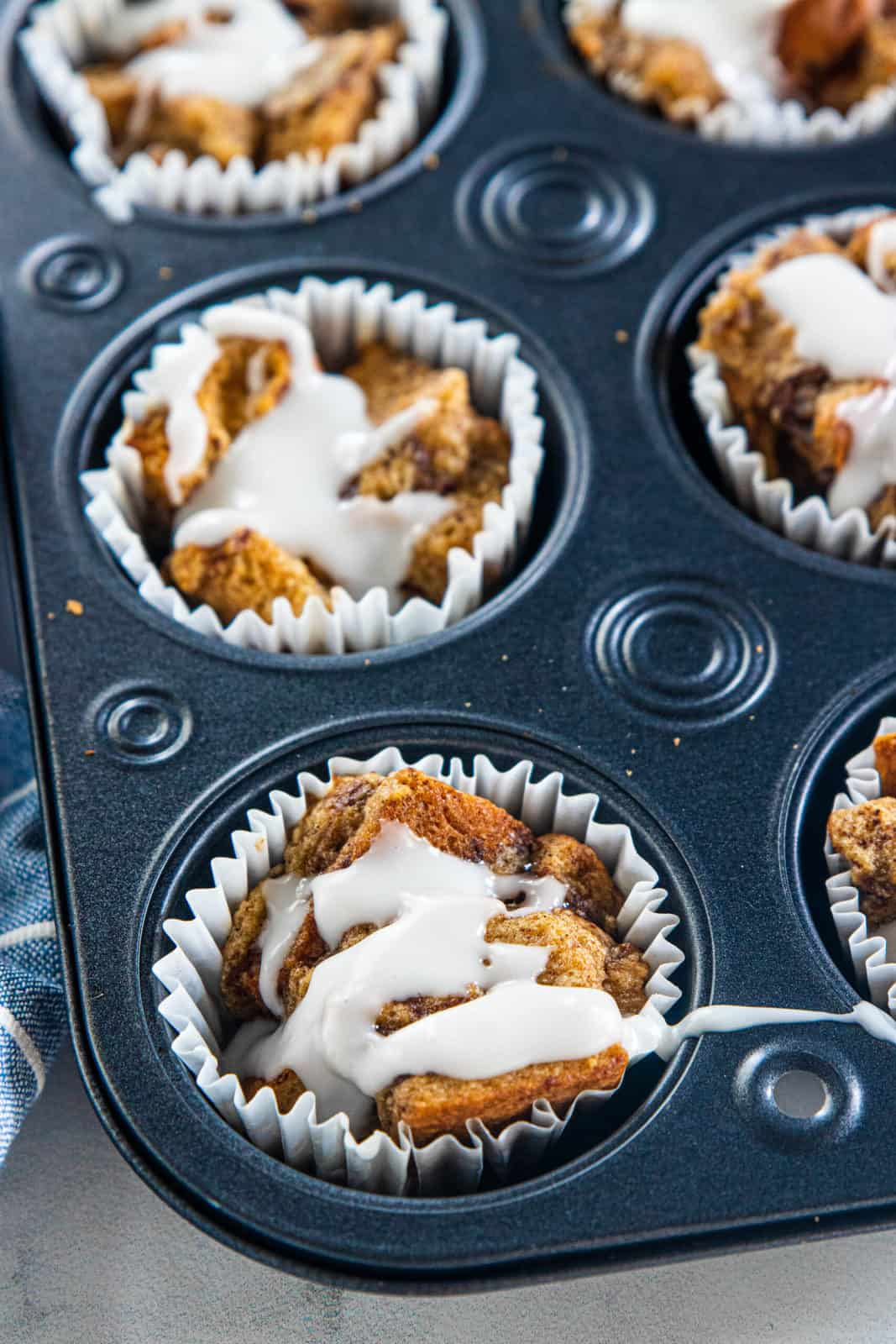Baked French toast muffins in a muffin tin with glaze drizzled over the top.