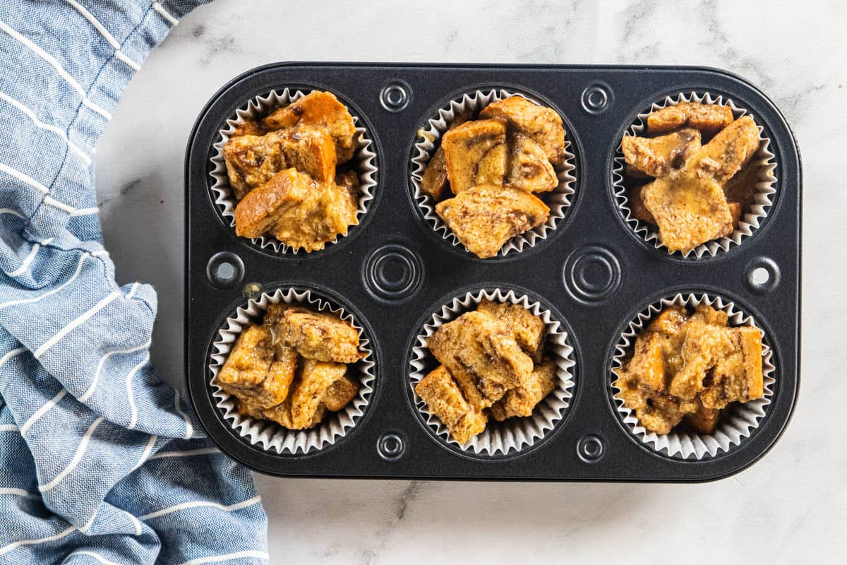 Baked French toast muffins in a muffin tin with a blue dish towel next to the tin all on top of a countertop.