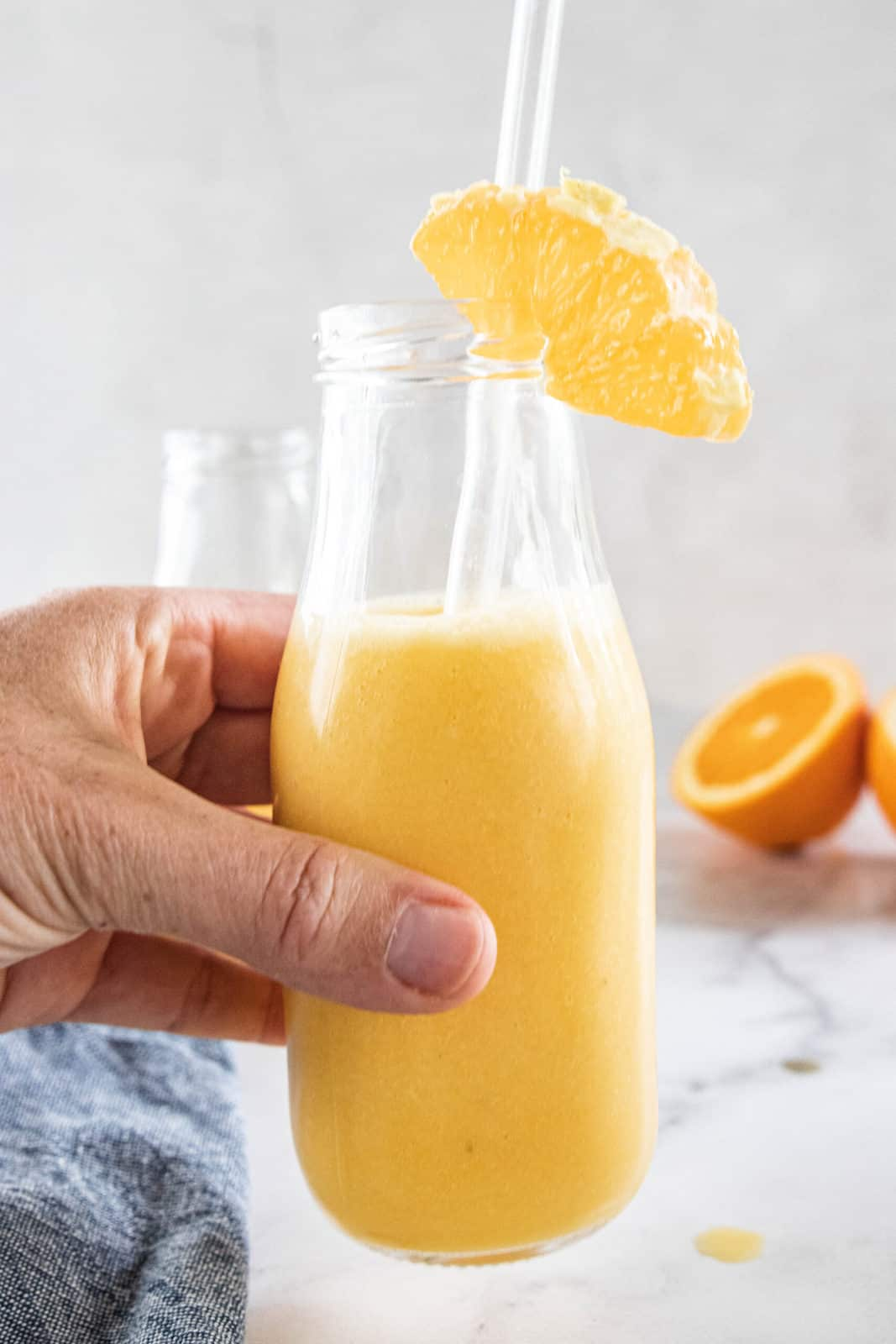 A hand holding a glass jar with a straw filled with orange smoothie.
