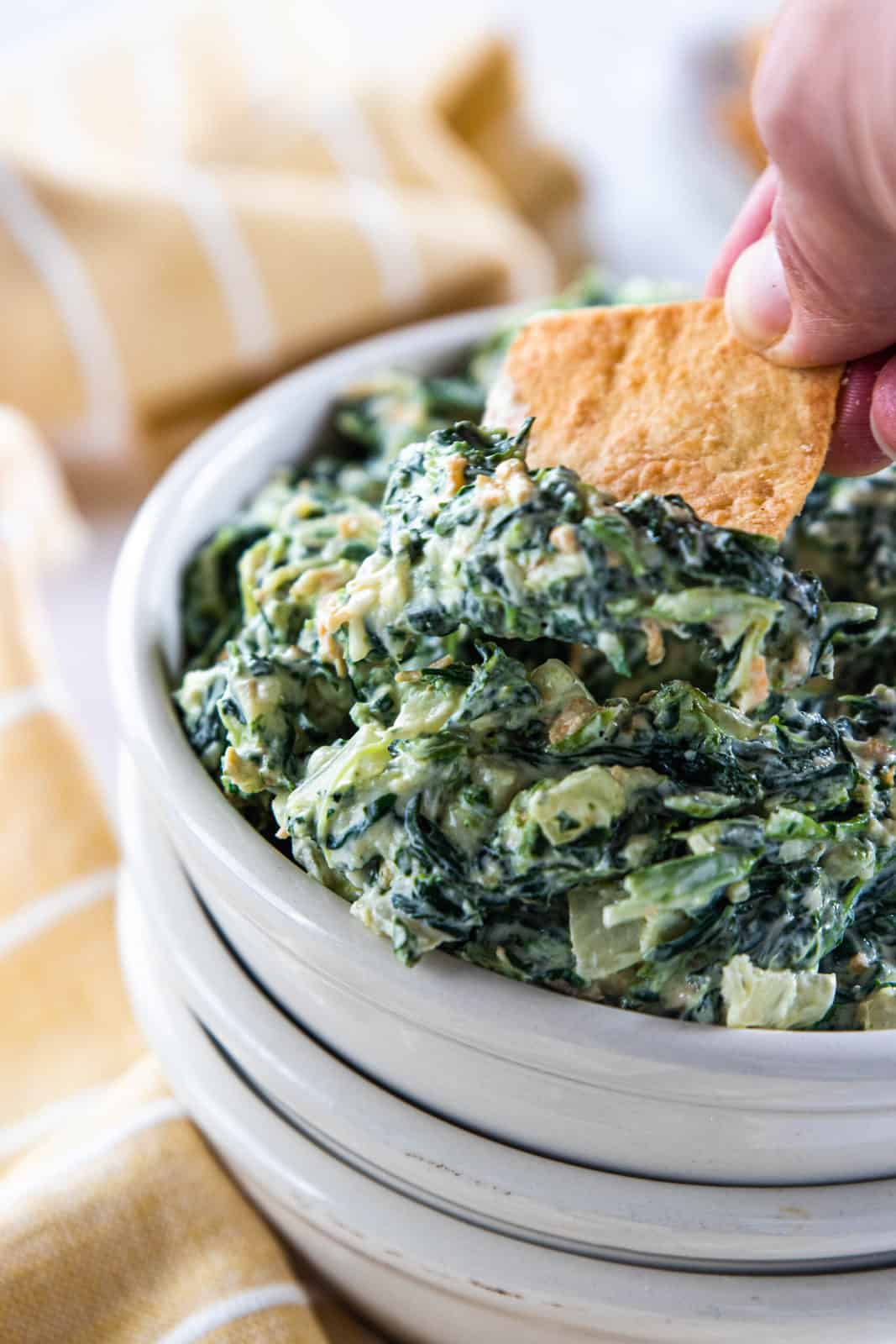 A hand scooping a pita chip into a white serving bowl filled with spinach dip.