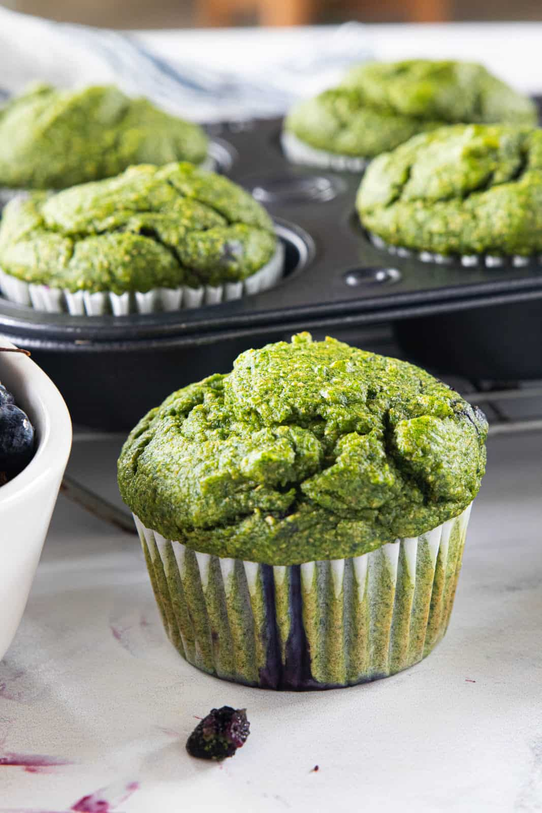 A spinach muffin cooling on a granite countertop with a muffin tin full of spinach muffins next to the single muffin along with a bowl of fresh blueberries.