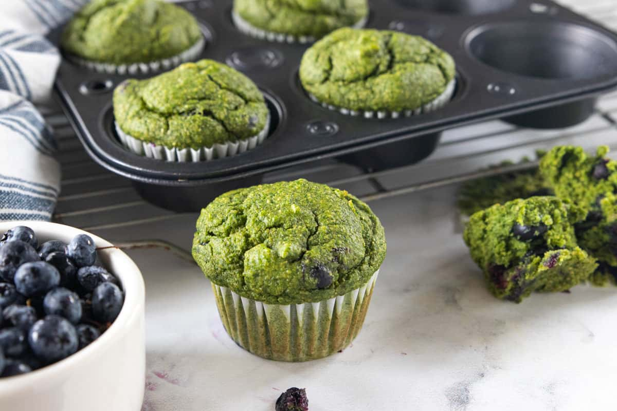 Spinach Muffins in a muffin tin with two muffins cooling on a granite countertop next to a bowl of fresh blueberries.