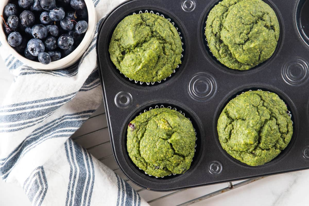 A muffin tin of cooked veggie muffins on a cooling rack next to a bowl of fresh blueberries and a dish towel all on top of a granite countertop.