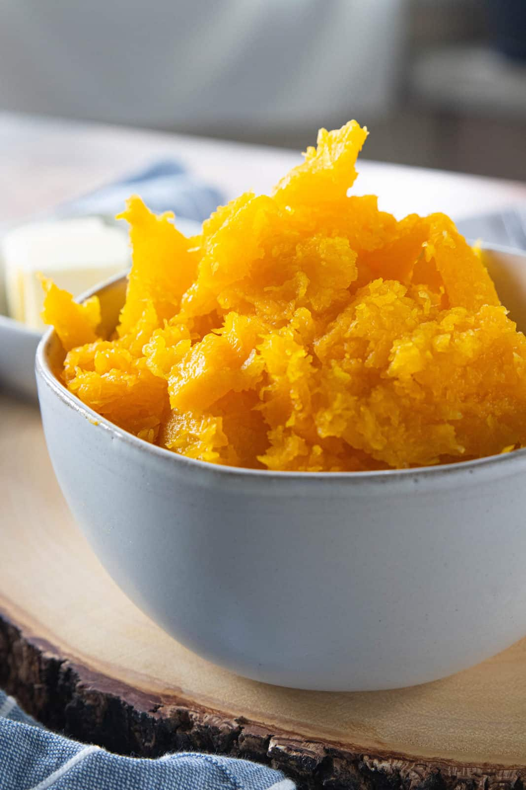 Steamed butternut squash in a white bowl.