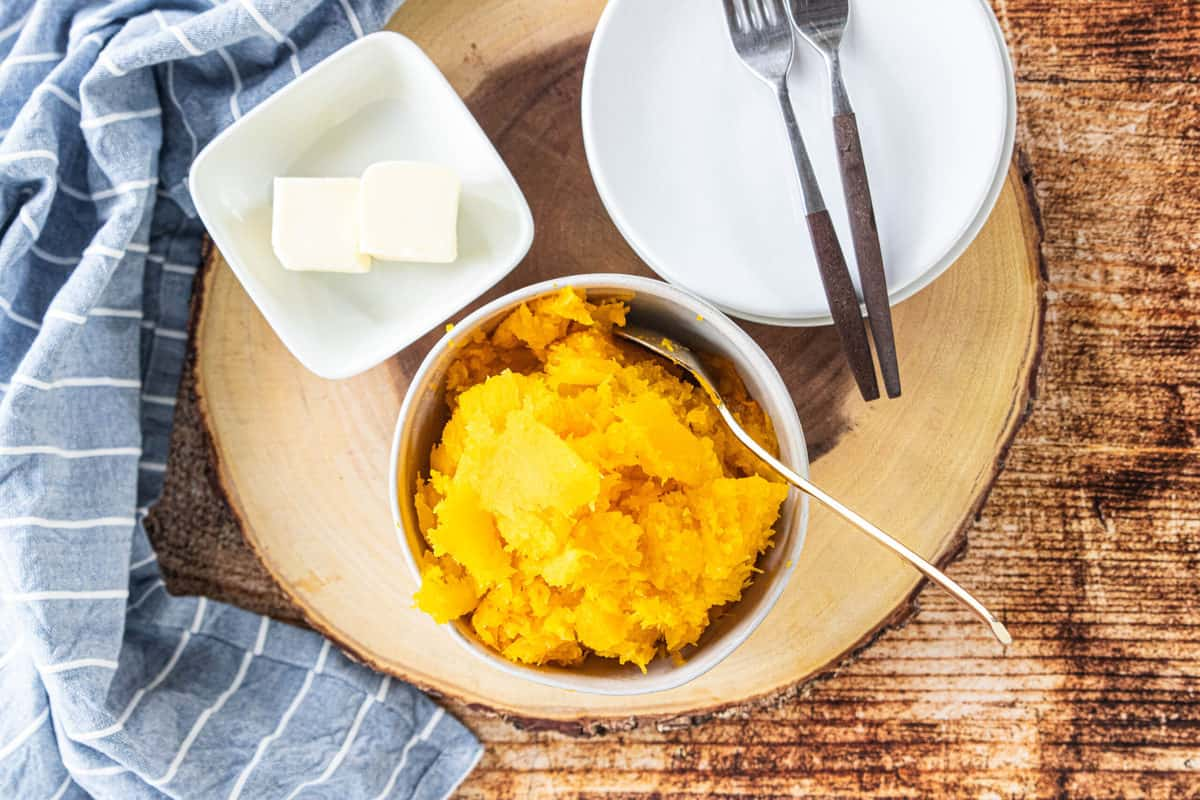 Butternut squash in a white bowl with a dish of butter, two plates and two forks next to the squash all on top of a wood round.