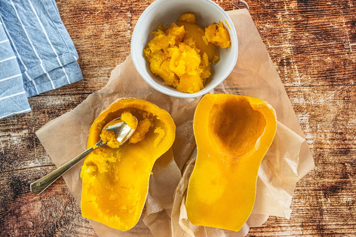 A microwave steamed butternut squash cut in half that is on top of brown parchment paper with a spoon that has scooped out squash into a white bowl.