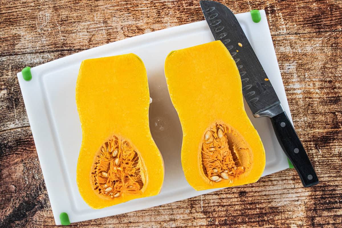 A butternut squash cut in half on top of a white cutting board with a knife on the cutting board all on top of a wood countertop.