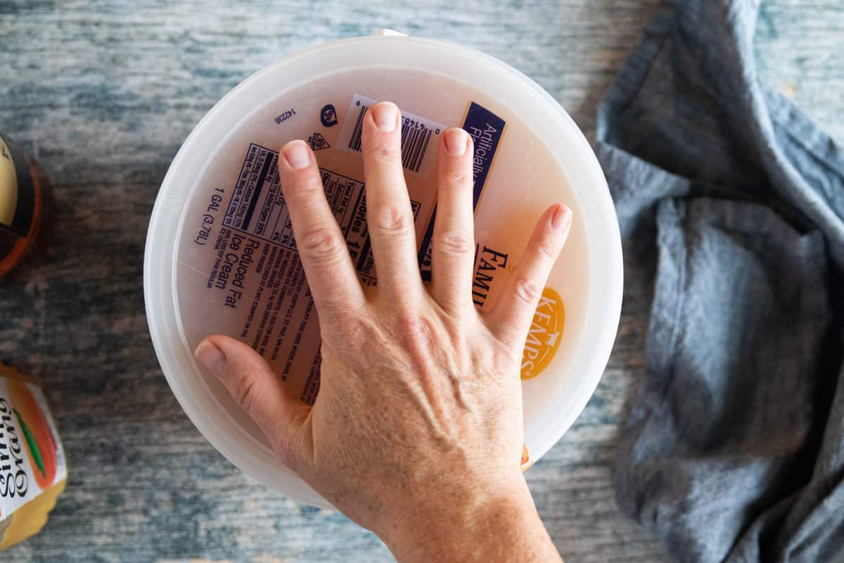 A hand placing a lid on to of an ice cream pail.