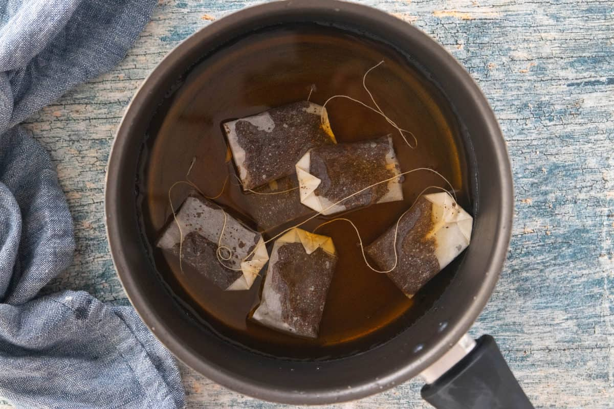 Six tea bags steeping in a large pot filled with boiling water.